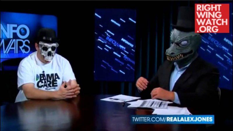 """Алекс Джоунс (с маска на влечуго) в маскарадна сцена """"разобличава истинската цел"""" на здравната реформа (Обамакеър) на Президента Обама. Маската на влечуго вероятно е реверанс към Британския му колега Дейвид Айк. Мъжът с маска на череп представлява Обамакеър. Източник: Right Wing Watch.org"""